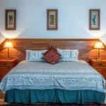 Bett mit Hellblauer Decke und rotem Kissen in der mitte. links und rechts vom bett sind lampen auf einem nachttisch. es befinden sich drei längliche bilder über dem bett an der wand.